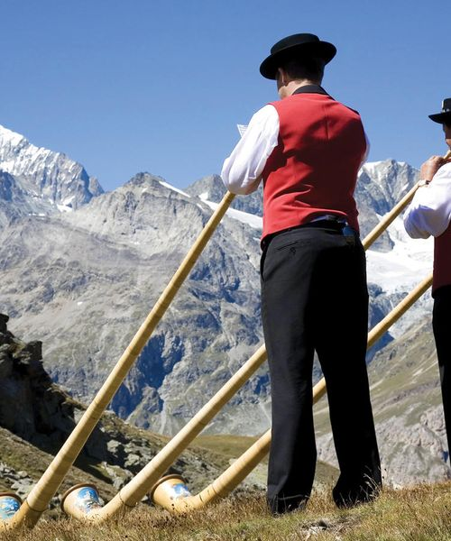three swiss men standing on mountain playing traditional swiss trumpets