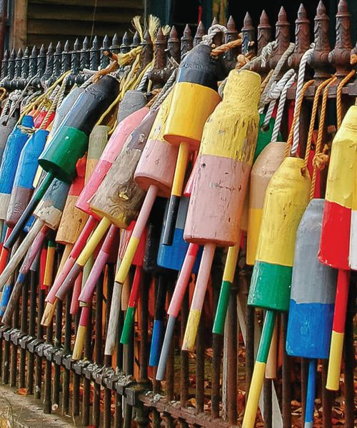colorful painted buoys hanging on fence