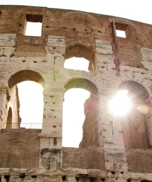 sun shining through window pane opening in colosseum in rome italy