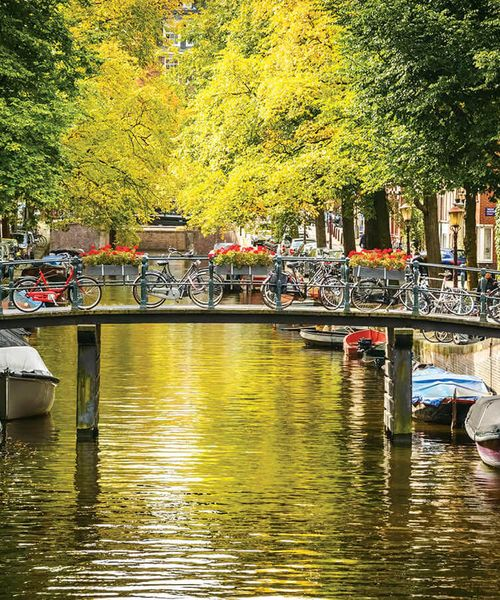 bridge lined with bicycles over canal filled with covered boats in amsterdam