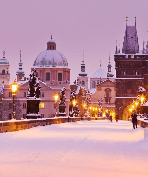 charles bridge covered in snow during the evening in prague