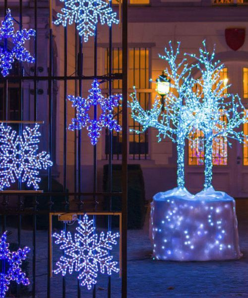 blue light shaped snowflakes hanging from metal fence at night