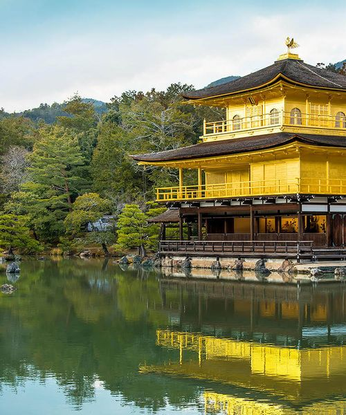 bright yellow temple of kinkaku ji on a river in kyoto japan