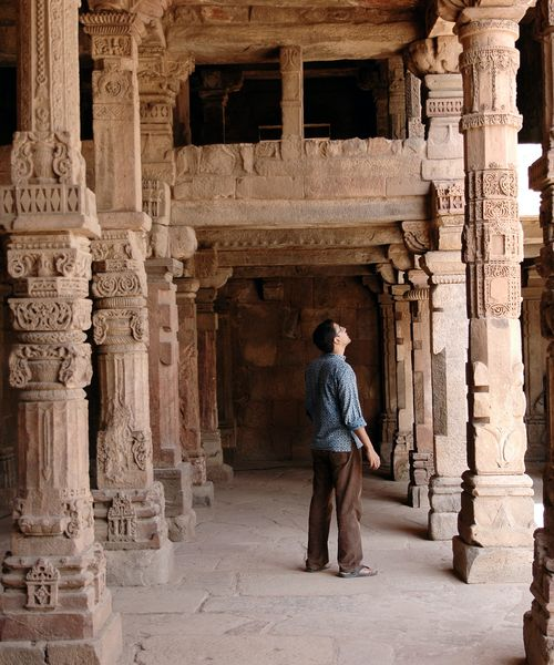 traveler looking up at the qutub minar in new delhi