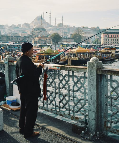 man fishing on a bridge in istanbul with the blue mosque in the background