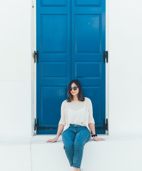 a woman sitting in front of a bright blue door on a traditional greek whitewashed building