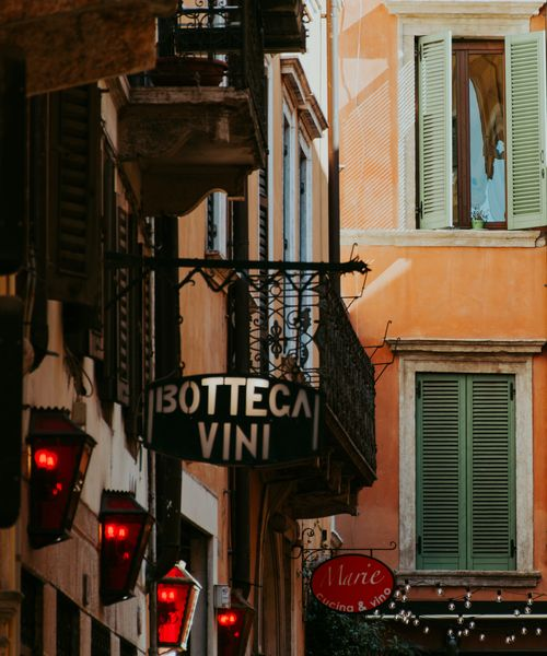 a sign for bottega vini on a colorful street in verona