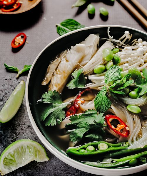 a bowl of vietnamese noodle soup with vegetables called pho