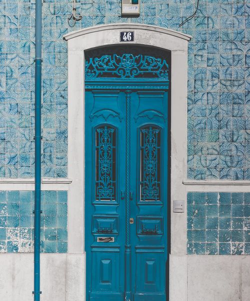 an ornate blue door on the street in portugal