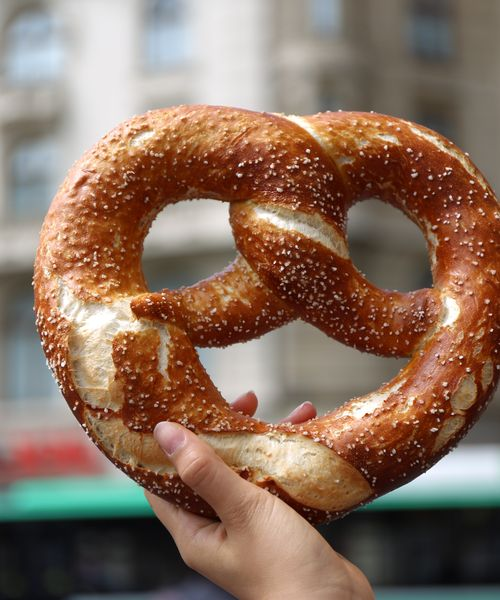 a hand holding up a large pretzel