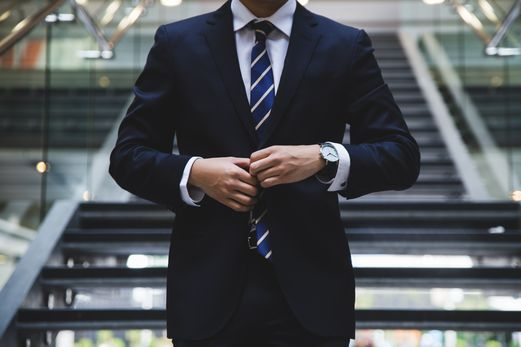 Man buttoning up suit in front of staircase