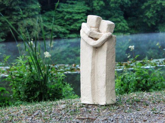 Skulptur in der Natur zweier Personen die sich umarmen