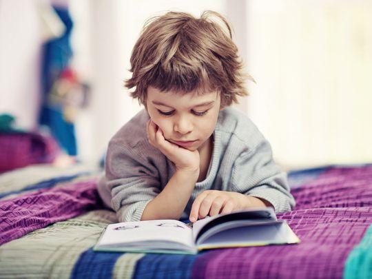 Junge liegt bäuchlings auf dem Bett und schaut in ein Buch