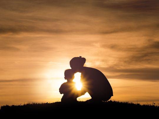Silhouette einer Mutter mit Kind vor einem Sonnenuntergang