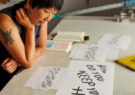 artist Christine Wong Yap in her studio looking at her work