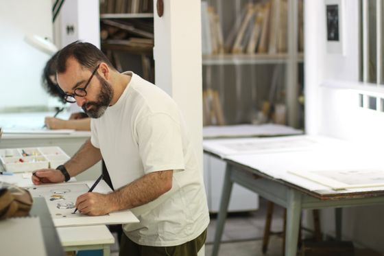 Artist Javier Calleja hand-finishing his prints at the printing house