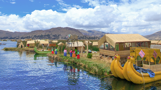 yellow boats in front of a village in lake titicaca peru