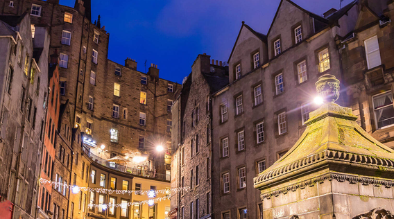 buildings lit up at night in old town edinburgh