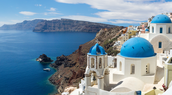 blue-domed buildings along the coast in santorini greece