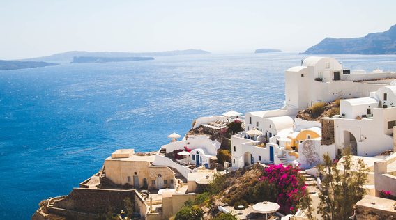 views of the aegean sea from the greek islands with white buildings in the foreground