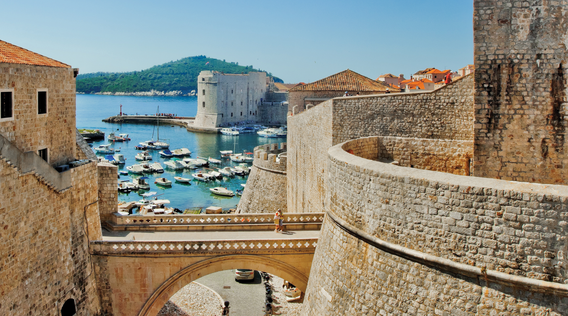 tan stone walls of dubrovnik with view of water