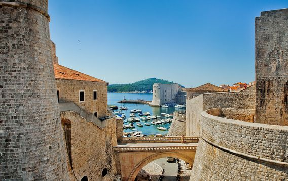 tan stone walls in dubrovnik leading down to a marina filled with sail boats