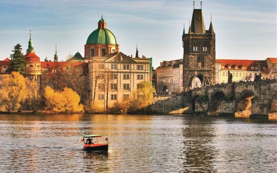 boat in vtava river in front of charles bridge in prague