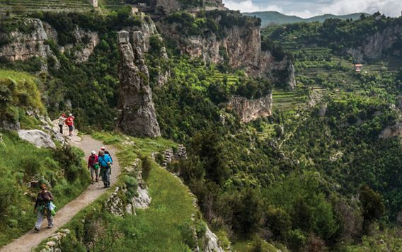 people walking along a cliff in italy