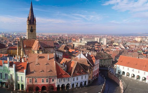 red roofed buildings surrounding clock tower in sibiu romania
