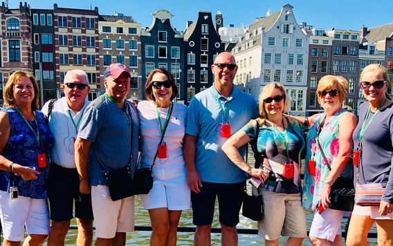 group of travelers in front of colorful homes in amsterdam
