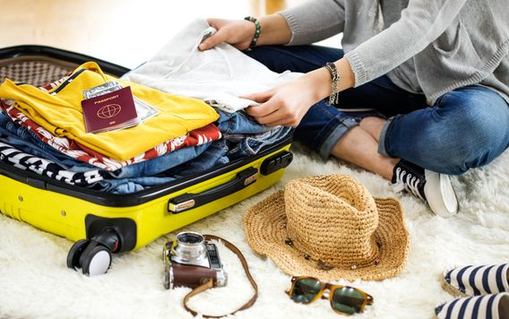 woman wearing black sneakers packing clothing in yellow suitcase