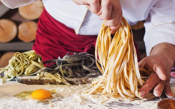 close up person in a red apron making of homemade pasta