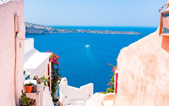cream colored stairs leading down to the blue ocean in greece