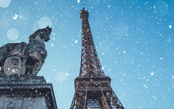 looking up at eiffel tower while its snowing
