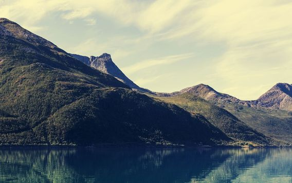 mountain range in norway reflecting in lake