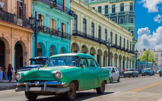 teal car driving down main street in havana cuba