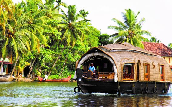 man in blue shirt driving house boat on river in kerala india