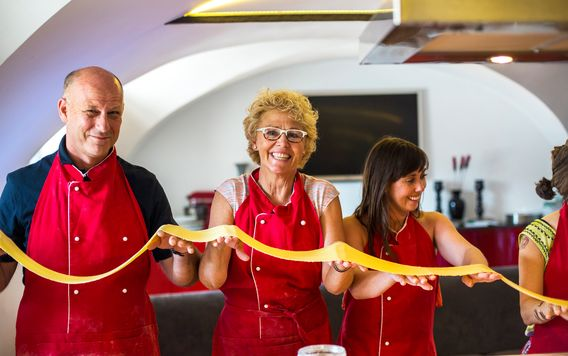 group of travelers holding fresh pasta at a cooking class in italy