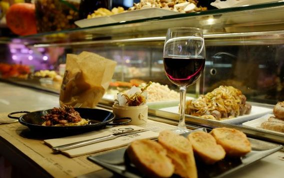 spanish tapas with a red glass of wine at spanish market