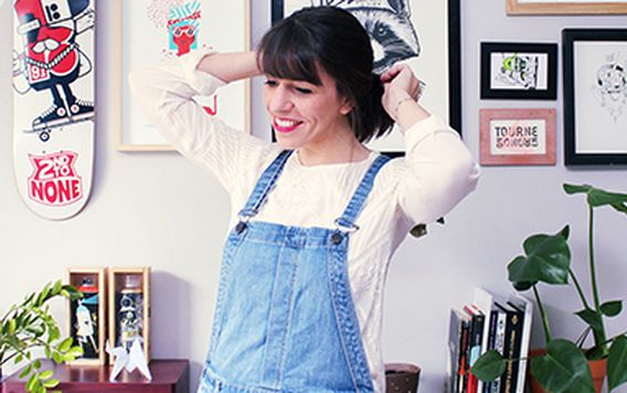 french illustrator maite franchi wearing jean overalls and a white long sleeve shirt in her studio