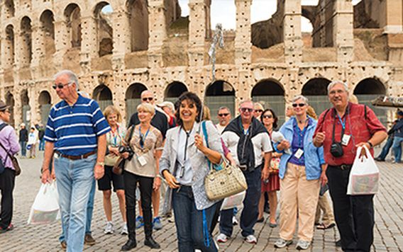 group of travelers following a tour guide outside the colosseum in rome italy