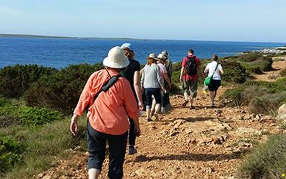 group of people walking on dirt path on the coast of spain