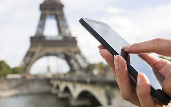 close up of a hand holding a black iphone in front of the eiffel tower in paris