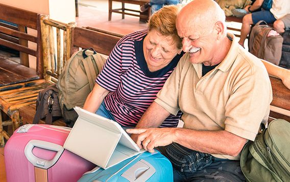 two elderly people looking at an ipad near some suitcase