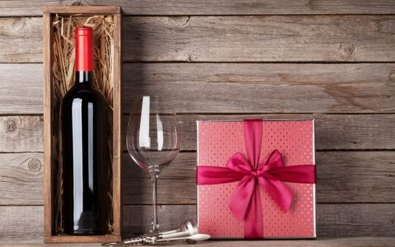 wine in a wood box next to a wine glass and gift box