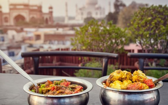 two metal bowls filled with curry on table in india