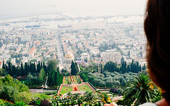 back of womens head looking down on bahaj gardens in haifa israel