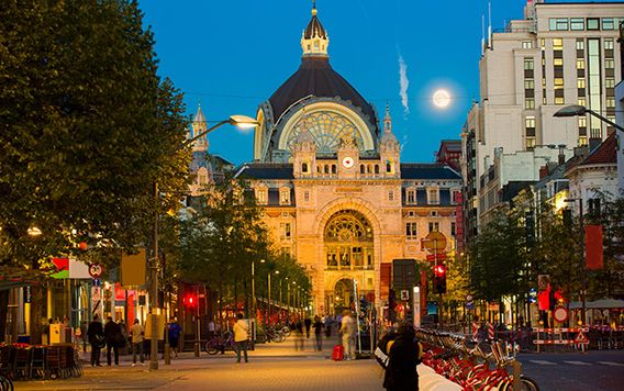 city of antwerp lit up at night with moon shining down on street