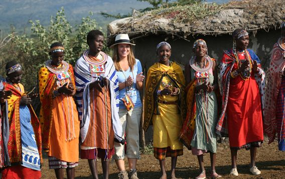 traveler maggie standing with the women in the masai mara tribe