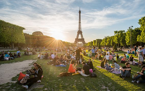 crowds of people sitting in front of the eiffel tower in paris on a sunny day